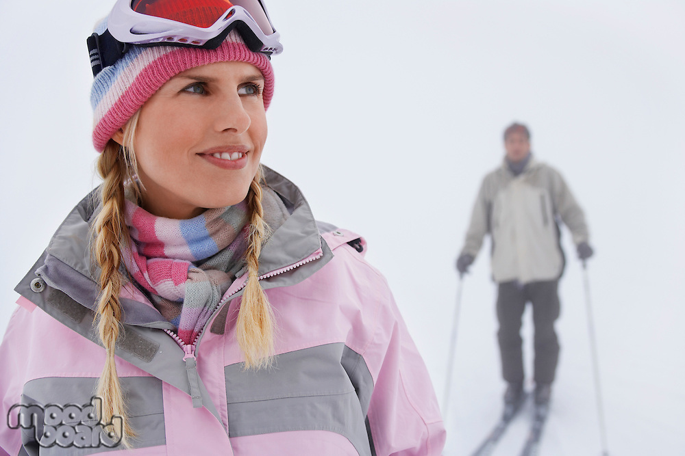Woman standing on ski slope man on skis in background