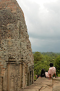Cambodian boy sitting at the edge of Angkor Wat temple