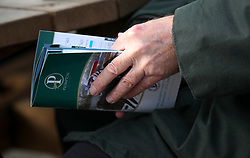 Detail of a racegoer reading the program ahead of the Injured Jockeys Fund Charity Raceday at Plumpton Racecourse.