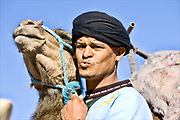 moroccan man with his camel in the atlas mountains