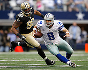 Dallas Cowboys quarterback Tony Romo (9) slips as he escapes New Orleans Saints defensive tackle Tom Johnson's (96) tackle at Cowboys Stadium in Arlington, Texas, on December 23, 2012.  (Stan Olszewski/The Dallas Morning News)