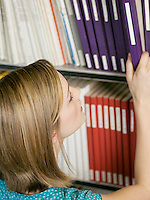 College Student Selecting Book From Shelf