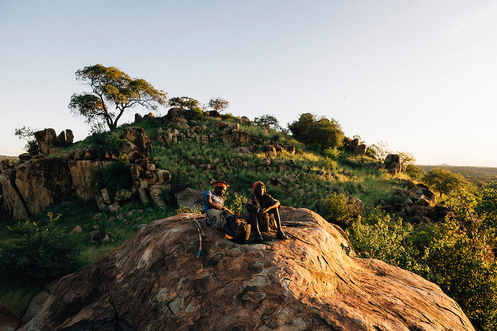 Piwa, a septuagenarian, and Benja, 20, of the Hazda tribe, sit on a rock at dusk, Yaeda valley, Northern Tanzania. Photo by Greg Funnell, March 2016