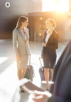 Businesswomen discussing plans while walking with their suitcase in airport