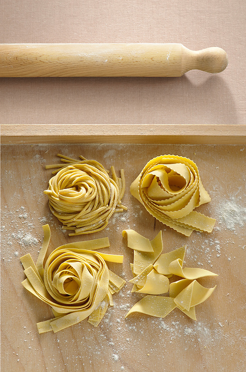 four fresh egg pasta shapes on a pastry board