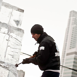London, UK - 11 January 2012: a sculpture carves a block of ice with his chisel during the Ice sculpting festival 2013 in Canary Warf.