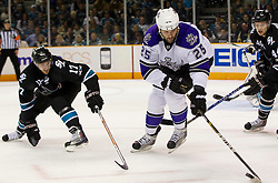 April 14, 2011; San Jose, CA, USA; Los Angeles Kings left wing Dustin Penner (25) controls the puck as San Jose Sharks center Torrey Mitchell (17) defends during the first period at HP Pavilion. Mandatory Credit: Jason O. Watson / US PRESSWIRE