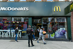 "© Licensed to London News Pictures. 13/05/2020. LONDON, UK. A delivery rider carries an order as the McDonald's fast food restaurant in Harrow reopens for ""McDelivery"" during the ongoing coronavirus pandemic.  The restaurant is one of 14 in the UK that the chain is partially reopening with a limited menu and delivery only.  Delivery is satisfied by third parties such as Uber Eats and Deliveroo.  Photo credit: Stephen Chung/LNP"