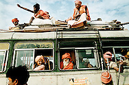 Khumb Mela, Hindu festival in Allahabad, India.<br /> A group of holy men are heading out on a long journey home. A salesman has attracted the passengers attention with his merchandise.