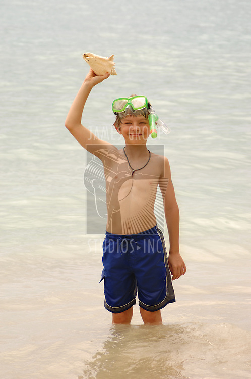 Young boy with snorkel and mask holding up a sea shell while standing in the sea