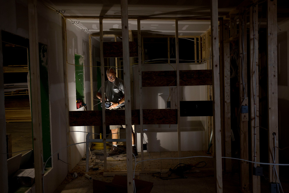 Patrick Caruso installs bathroom plumbing in a modular home at the Vermod Homes manufacturing facility in Wilder, Vt., on Aug. 28, 2017. Caruso, who retired as a full-time plumber, said he installs two bathrooms a week for the company. (Photo by Geoff Hansen)