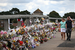 © Licensed to London News Pictures. 02/09/2015. Shoreham, UK. People look at floral tributes placed on a bridge near the site of the crashed Hawker Hunter fighter jet. The aircraft crashed while performing at the Shoreham air show on August 22, 2015 killing 11 people on the ground. As an inquest into the deaths opened today in nearby Horsham, the name of the last of the victims Graham Mallinson was released.  Photo credit: Peter Macdiarmid/LNP