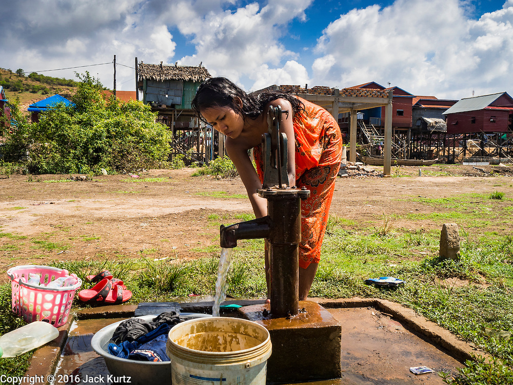 31 MAY 2016 - SIEM REAP, CAMBODIA: A woman does her laundry in a small village near the Tonle Sap lake south of Siem Reap. The area is experiencing a record breaking drought and relying on emergency wells for domestic water. The village normally floods in the rainy season, and their homes, built on stilts nearly 30 feet above the ground, accommodate the floods, but it's not clear  yet if the village will flood this year. Officials hope the rainy season starts in coming weeks.    PHOTO BY JACK KURTZ