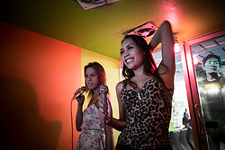 Aen and her friend at a Karaoke place in the suburbs of Bangkok. Transgenders, &quot;Katheoys&quot; live in a kind of parallel universe within Thai society.<br /> <br /> Katheoys are biological men who have been born with distinctifly female hearts and minds. Some choose to have their anatomy 'corrected' whilst others are content to dress in womens clothing or simply give free reign to their effeminate mannerism.