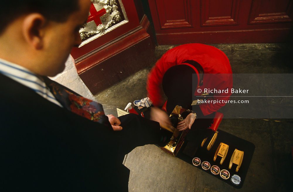 A businessman stands over a Victorian-style shoe-shiner in a corner of Leadenhall Market in the City of London. His black shoe is resting on a small brass plinth for the leather to be buffed up with the help of Kiwi polish and the efficient speed of a good brushing technique with the final stage being a dusting to bring the best reflective shine. Their relationship is that of paying-customer and servant and we look downwards from the perspective of the wealthier man, a superior view that the client feels when paying for such a service. Wearing a red uniform, the shoe-shiner is on bended-knees, his weight resting on a soft, red cushion, protection from the cold, hard pavement while looking down, concentrating on the job in hand.