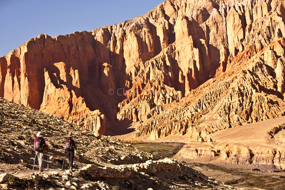 Jodie Bell & Kinde Nebeker approach the red stone cliffs of Dhakmar in Nepal's Mustang Region.
