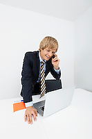 Happy businessman using cell phone while looking at laptop in office