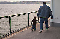 A black man and his young son walk along the rail in pleasant weather on a Washington State Ferry in Rich Passage of Puget Sound, panorama
