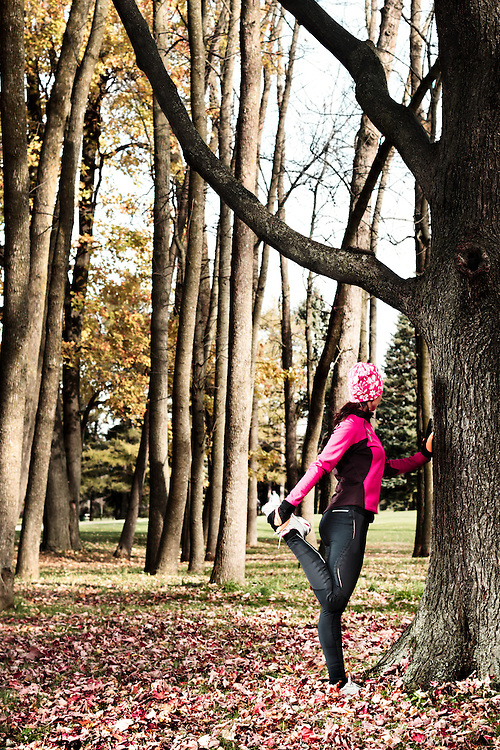 Young woman in fall season stretching during an outdoor workout.