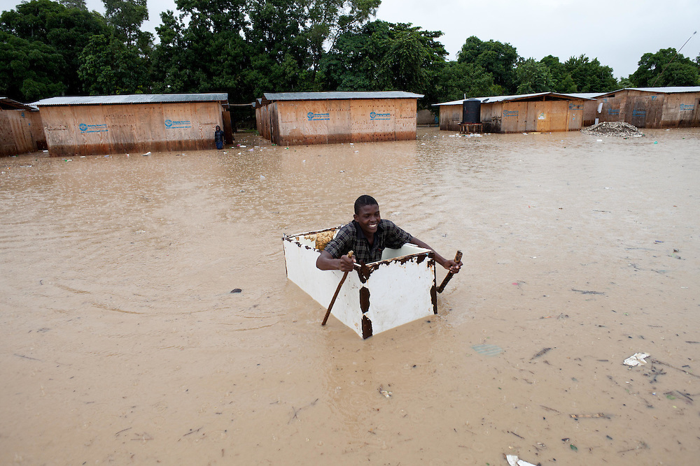 Sonson St. Jean, 18, uses an old refrigerator as a boat to move around an area flooded by rain from hurricane Tomas.