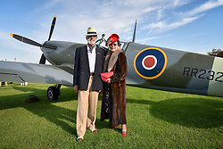**CAPTION CORRECTION. Picture originally sent with wrong date. Picture was taken TODAY 11/09/2015** © licensed to London News Pictures. 11/09/2015<br /> Goodwood Revival Weekend, Goodwood, West Sussex. UK.<br /> The Goodwood Revival is the world's largest historic motor racing event. Competitors and enthusiasts dress in period fashions recreating the glorious days of the race circuit.<br /> Pictured. Mr & Mrs Brewin from Northants dressed in period clothing pose in front of a MKHF IX Spitfire.<br /> Photo credit : Ian Whittaker/LNP