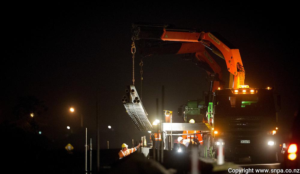 Contractors fit a clip on bridge to carry the new Unison Fibre across the Ahuriri Estuary, Napier, New Zealand, Tuesday, 22 January 2013. Credit:SNPA / John Cowpland