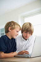 Two brothers using laptop on table at home