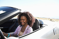 Woman driving convertible on desert road