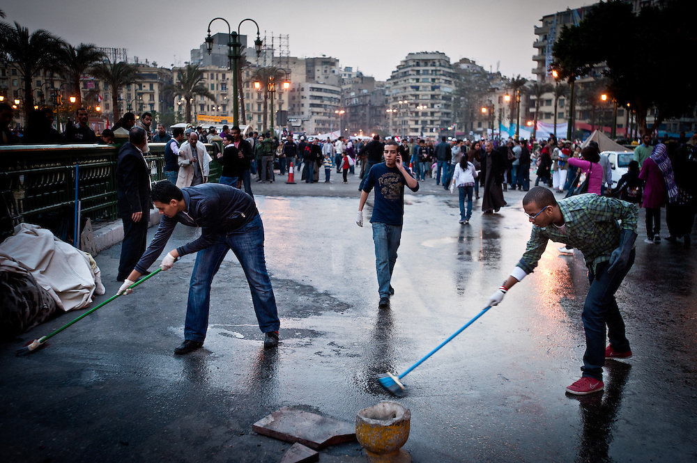 A volunteer Egyptian cleaning crew scrubs the street in Tahrir Square the day after protesters successfully brought about the resignation of President Hosni Mubarak, who ruled the country for thirty years. Volunteers flooded the square on Saturday; they repainted the sidewalk markings, swept and scrubbed the streets, and collected garbage until late in the evening.