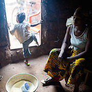 Marie Madeleine Ouattara waiting for a pot to boil as she cooks toh, a local staple made from millet, for the midday meal in the village of Toussiana in the Hauts-Bassins region of Burkina Faso, on 22 February 2016. She lives in an extended family household, and she and her husband's brother's wife take it in turns to cook.