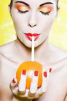 beautiful caucasian woman portrait orange drink with a straw studio on yellow background