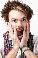 Portrait of angry young man screaming against white background