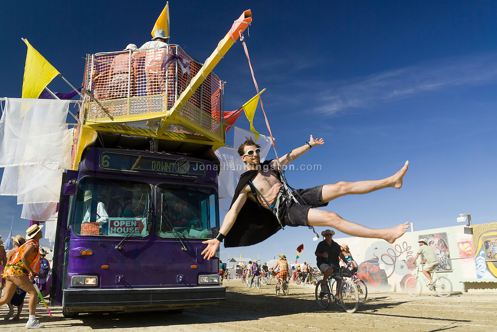 BLACK ROCK CITY, NV:  Participants of Burning Man festival climb aboard a bus to take a tour of the temporary art instillations around Black Rock City, Nevada.  The bus, a work of art itself, dangles one Burning Man participant as 'bait' from a climbing rope in front of the driver.  Participation in the event is encouraged for every member of Black Rock City.