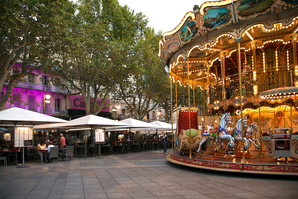 While strollers check out the evening's offerings at the cafes, the carousel adds a touch of fun to the Place de L'Horloge in Avignon, France.