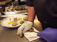 """Bob Wilson shucks oysters for their """"Buck a Shuck"""" promotion at Faro Italian Grille in Weirs Beach.  (Karen Bobotas/for the Laconia Daily Sun)"""