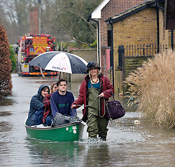 Mum gives her family a lift to dry land on Ham Island, by the River Thames at Old Windsor, United Kingdom, Saturday, 8th February 2014. Picture by David Dyson / i-Images