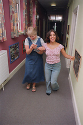 Teenage girl with physical disability walking with support of carer along corridor of residential respite care home,