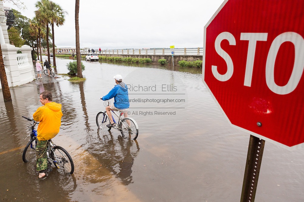 Bicyclists pause to view the floodwater along the Battery in the historic district as Hurricane Joaquin brings heavy rain, flooding and strong winds as it passes offshore October 4, 2015 in Charleston, South Carolina.