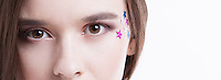 Cropped image of beautiful young woman with stars on her face against white background