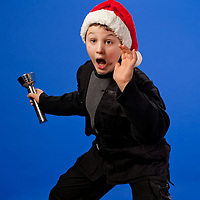 Boy with a santa hat and flash light acting surprised at what he is seeing