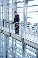 Businessman by railing in modern building