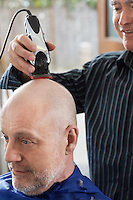 Barber shaving mans head in barber shop