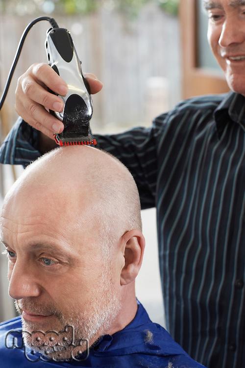 Barber shaving mans head in barber shop