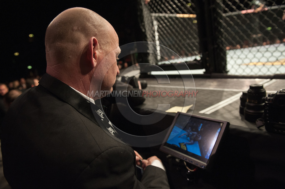 """LONDON, ENGLAND, FEBRUARY 16, 2013: Judge Chris Watts observes fight action on a monitor during """"UFC on Fuel TV 7: Barao vs. McDonald"""" inside Wembley Arena in Wembley, London on Saturday, February 16, 2013 (© Martin McNeil)"""