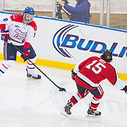 A.J. White #18 of the UMass Lowell Riverhawks and Kevin Roy #15 of the Northeastern Huskies in action during the Frozen Fenway game between The Northeastern Huskies and The UMass Lowell Riverhawks at Fenway Park on January 11, 2014 in Boston, Massachusetts.