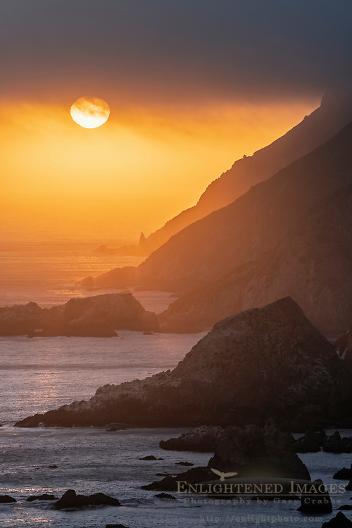 Setting sun dips below coastal clouds over the headland cliffs at Point Reyes National Seashore, Marin County, California