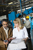 Man and woman using calculator and checking newspaper in factory