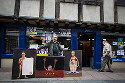 © Licensed to London News Pictures . 19/11/2014 . Kent , UK . Political artist KAYA MAR with a portrait of David Cameron drowning in a red sea of UKIP , alongside portraits of Nigel Farage and Ed Miliband , outside the UKIP shop on Market Street , Rochester , this morning (19th November 2014) . The Rochester and Strood by-election campaign following the defection of sitting MP Mark Reckless from Conservative to UKIP . Photo credit : Joel Goodman/LNP