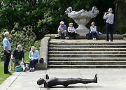 © Licensed to London News Pictures. 24/05/2012. Waddesdon, UK. People rest near to  a Anthony Gormley figure seen lying on the floor. People enjoy the warm weather amongst an exhibition of contemporary sculpture at Waddesdon Manor, Buckinghamshire, today 24th May 2012. The exhibition is being held by Christie's as part of a private sale. Photo credit : Stephen Simpson/LNP
