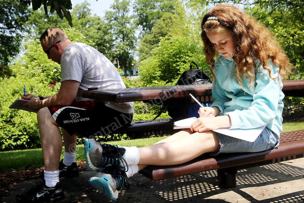 Co-cordinator Jeremy Hyler and a student work on their writing outside the Fabiano Botanical Garden during the Chippewa River Writing Camp photo by Emily Mesner